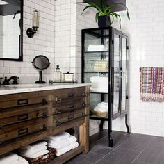 A vintage cabinet is transformed into a bathroom vanity that brings a dash of eclectic glamour to a modern bathroom.