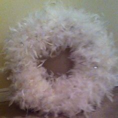 Feather wreath made from a pool noodle and 10 white feather boas from the dollar store