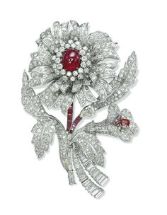 A RUBY AND DIAMOND BROOCH  Designed as a stylized flower with pavé-set diamond petals and leaves centering upon a cabochon ruby pistil mounted en tremblant, to the calibré-cut ruby and baguette-cut diamond stem, the smaller flower also with a ruby pistil, mounted in platinum, 11.0 cm
