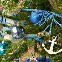 A nautical Christmas tree with anchor ornaments and blue ornaments.