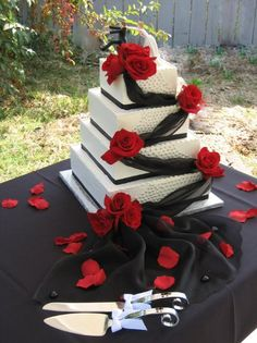 4 tiered stacked square cake. Draped with elegant black fabric accentuated with dark red roses at each corner. The fabric spills on the the table and flows out dramatically, sprinkled with rose petals. The fronts of the cakes are also decorated with silver dragees.