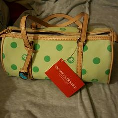 Dooney and Bourke barrel bag green circle db Never used but dirty from being in storage. It's just minor dust/debris could be cleaned with ivory soap. Interior is in perfect condition. Comes with registration card. The bag was bought as a gift and I moved and didn't remember having it until I cleaned out my storage unit. I reflect the discount of having to clean it in the price :) Dooney & Bourke Bags Hobos