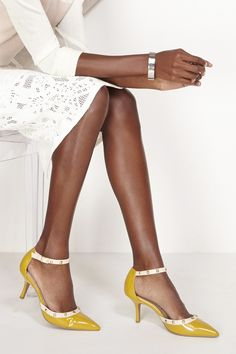 Mustard yellow, pointy mid heel pumps with chic studs and ankle straps