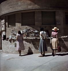 Robert Capa © International Center of Photography 1950 ISRAEL, Jerusalem, 1949-1950. Women brousing at an outdoor magazine...
