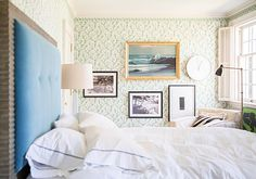 In this contemporary eclectic bedroom, a white modern clock and framed artworks of nature embellish the patterned green walls.