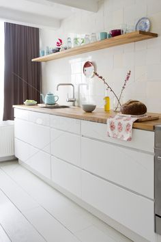 white kitchen with wood counter and shelf