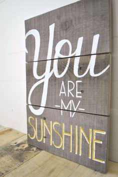 "This piece is handmade using reclaimed wood slats. It has been lightly sanded to retain the original distressed texture of the wood. The phrase ""You are my sunshine"" has been hand-lettered and hand-painted in white and yellow acrylic paint."