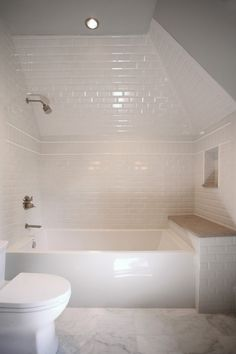 Amazing attic bathroom features glossy white bathtub tucked under dormer accented with white beveled subway tile surround and a stripe of small vertical tile border as well as a tiled shower niche over a built-in bench atop honed Carrera Bella Marble tiled floor.