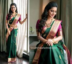 Nabha natesh dolled up in a dark green Kanjeevaram saree that has purple and gold zari border by RS Brothers for RS brothers store inauguration. Bridal Sarees South Indian, Indian Bridal Outfits, Wedding Silk Saree, Indian Bridal Fashion, Indian Dresses, Indian Wedding Sarees, South Indian Bride, Wedding Saree Blouse Designs, Half Saree Designs