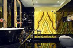 Brilliantly backlit onyx in the bathroom adds gold to the dark space - Decoist