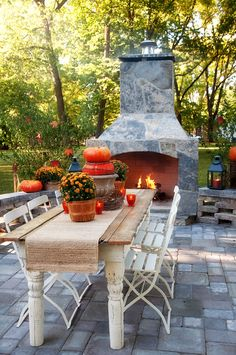 Outdoor patio with pavers, a large wooden table with chairs and stone fireplace for alfresco dining. Love it~!