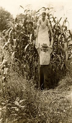 A woman on a farmer's shoulder emphasizes a corn crop's height in Minnesota, 1916. National Geographic