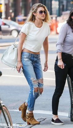 Gigi Hadid wears a white crop top, distressed blue jeans, suede ankle boots and a white bucket bag.