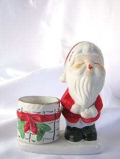 Kissing Santa! Possibly one of a pair. Vintage 1970s Luvkins Santa Christmas votive candleholder stands next to a Christmas basket