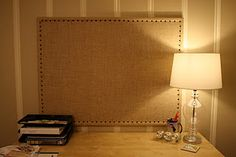 Make a plain jane corkboard beautiful with some burlap and furniture tacs.