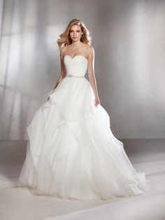 Spectacular ballgown wedding dress in tulle with an incredible beaded waistband. A design with a very full skirt in asymmetrical layers of tulle in the form of flounces. It features a bodice with a sweetheart neckline and open back in draped tulle.