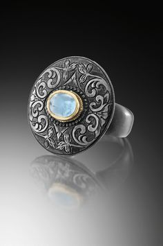 David Giulietti. Spanish western scroll engraving and an aquamarine cabochon set in 18ky gold. Blackened sterling silver ring.