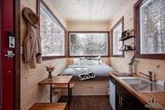 The Vantage by Tiny Heirloom. Cozy tiny cabin on wheels with lots of windows.