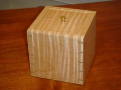 This 5 cube tiger maple keepsake box is designed to hold a smaller very nice gift for my wife. The construction is hand cut dovetails with no metal or mechanical fasteners other than the small brass knob. The finish is three coats of low gloss clear tung oil with a coat of wax.