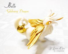 Dragon - fantasy sculpture / miniature   First in the Goldwing Dragon series, Belle has a cream-white body, bright golden wings and eyes, curled horns, defined scales on her breast and an adorable little bell (mobile) which she holds with her tail. Entirely made by hand and of original design,...