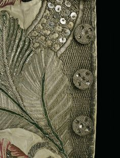 CLOSE-UP OF ANTIQUE CLOTHING    BUTTONS, EMBROIDERY WITH METAL THREAD