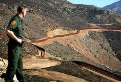 Border Patrol spokesman Jerome C. Conlin gazes across the base of Otay Mountain at a recently completed stretch of the U.S.-Mexico border fence.  The 3.6-mile barrier through rugged terrain east of San Ysidro cost about $57 million to construct.  Don Bartletti
