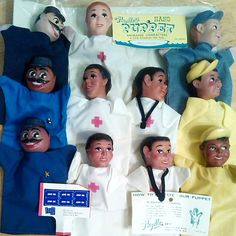 """Hazelle's 100 Series Hand Puppets """"Community Workers Series"""" was a set of four. Before the set on the bottom row arrived today, I had no idea they would be different costumes from the others in my collection. Notice the """"Policeman"""" (left) and the """"Worker"""" (right) have three different colors of fabric. I don't have a pink """"Doctor"""" yet. Notice the shape of the stethoscope on the two doctors are different shapes. There are two """"capper"""" cards showing the front (above) and back with instructions…"""