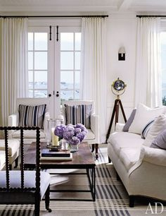 """Interior designer Victoria Hagan decorated an 8,000-square-foot Shingle Style summer house on Nantucket for a couple and their three children. The living room features striped pillows on white-duck-covered furniture, blue cashmere throws, and a custom-made blue-and-white-plaid rug (""""I adjusted its scale and pattern to the room,"""" she says); breezy white draperies frame the French doors, which open to views of the harbor."""