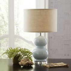 Courtland Table Lamp | The Courtland Table Lamp's sculptural silhouette and ceramic base create an eye-catching look, while its neutral drum shade helps make it a versatile styling choice.