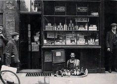 Het kleinste winkeltje in Londen, een schoenenverkoper in een 1,2 vierkante meter grote schoenenwinkel, 1900.