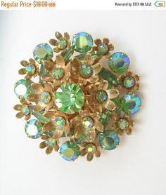 Vintage Rhinestone Brooch Peridot Green AB Aurora Borealis layered This vintage pin has cupped Ab glass rhinestones, textured flower petal cups,