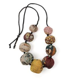 Silk Kantha Convertible Necklace by Mieko Mintz . Soft fabric beads are sewn from vintage saris, stitched with kantha embroidery, and filled with lightweight cotton batting, creating a necklace that is both bold and fun. Silk cord has glass beads on the ends allowing the necklace to be convertible from a choker to 36
