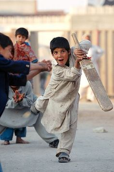 16. A boy happily playing cricket with his friends.