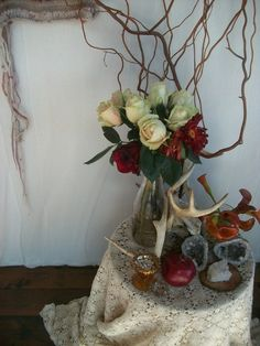 Altar-like decor. How beautifully the twigs play off the perfect roses.