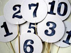 Wo sitzt wer? Tischnummern passend zu den Hochzeitsgirlanden als einzelne Scheiben, beidseitig mit Zahlen bedruckt auf einem Holzspieß. Jedes Za
