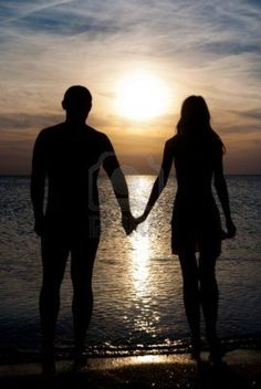 Young Couple Silhouette On A Sea Beach Holding Hands And Looking.. Royalty Free Stock Photo, Pictures, Images And Stock Photography. Image 18488154.