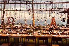 There's no such things as too many lights, edison lights, with cool marquee initials, and funky metal chairs. Cool Wedding style #loveatfirstlights
