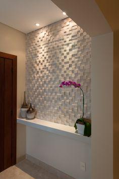 A falta de espacio, una pequeña balda hace las veces de consola. El revestimiento texturado de la pared se potencia con focos de techo colocados muy cerca de la pared, para que la luz rasante resalte los volúmenes del revestimiento.