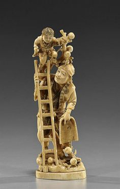 """Antique Japanese carved and lightly stained ivory okimono; depicting a man and boy with ladder and picking fruit, signed in inlaid red lacquer reserve, Circa 1900; H: 8 7/8"""""""
