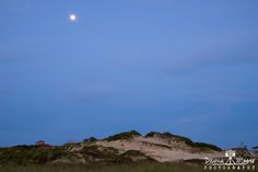 "Full Moon Setting over American Beach Dune, Amelia Island, Florida Dunes commonly begin as piles of sand accumulated in the lee of beach debris such as piles of seaweed (especially Sargassum), clumps of salt marsh straw, and a host of human refuse (fishing nets, bottles, timbers). Beach debris slows down the wind or blocks it, causing sand to accumulate in the wind ""shadow"" of the object. Eventually, dune grass seeds (especially Sea Oats) find their way to the new piles of sand, germinate…"