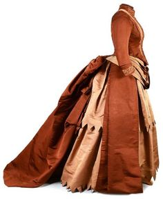 Day dress, 1885. Café au lait and brown ottoman. Bodice has the look of an open jacket; re-embroidered collar with a trompe-l'oeil lace effect. Asymmetrical skirt in two large swags with sawtooth hem, draped into train in back. Drouot Auctions via The Ornamented Being