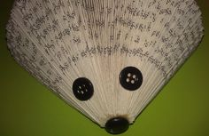 I will present to you a creation very easy and fun to do which moreover will be very pretty! This is a hedgehog in paperback. This is a practical activity to do with children. To do this hedgehog, you need : - A book with about a hundred pages. - Three buttons : two identical small black buttons and one slightly larger black too. - Some glue. - A little bit of patience.