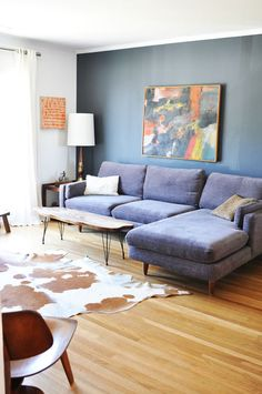(Inspiration)  blue couch, fun art, cow hide (again) accent wall