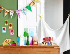 Bunte Partydekoration für einen Kindergeburtstag aus Wimpeln, Plakaten und Einladungskarten in einem hellgrünen Raum