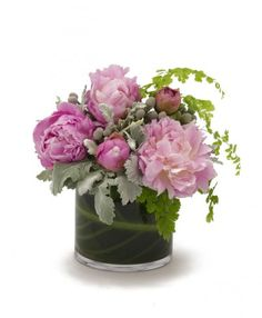 This sweet arrangement of light pink peonies is perfect for that special girl in your life. It features pink peonies with a touch of silver dusty miller and maiden hair ferns and is designed in a leaf lined glass vase. $85.00