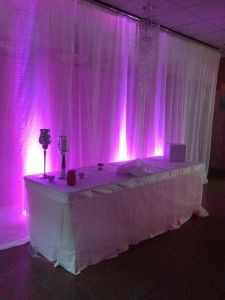 White Pipe and Drape with Purple Uplights at The Garden Room by Deckci Decor