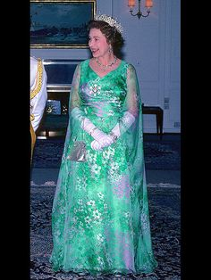 Also spotted on her stylish tour of the Middle East was this psychedelic green-and-purple printed gown, worn with the same silver bag and elbow-length gloves in Oman. Pretty picture for Queen Elizabeth II. God Save The Queen, Hm The Queen, Royal Queen, Her Majesty The Queen, Elizabeth Taylor, Queen Elizabeth Ii, Tilda Swinton, Maria Callas, Ute Lemper