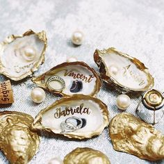 These gold painted oysters with @lhcalligraphy are stunning! Perfect for a seaside #wedding #tablescape and a lovely take home gift with your guests names.  Image by @abbyjiu  Learn more about Laura's #calligraphy talents in our #FineArtCuration : DIRECT LINK IN PROFILE by weddingsparrow