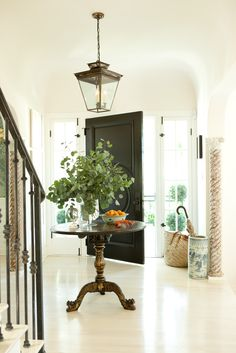 Hollywood Hills No. 1 - Mark D. Sikes--Large bright foyer with lantern, pedestal table, and striking black door.