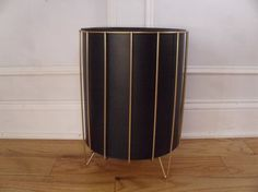 This metal plant holder is gold tone and features an atomic design. The insert is (black) metal and has a bit of weight to it. The plant holder